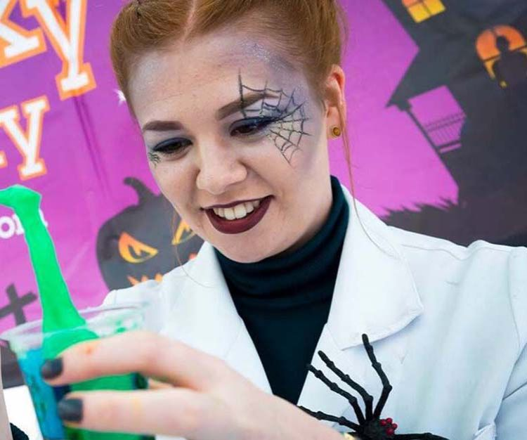 A mad scientist with a spider web drawn on her face playing with green slime in a cup