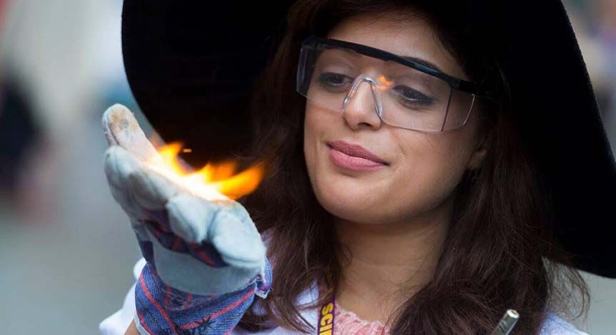 A female mad Scientist wearing a black hat holding fire in her hand