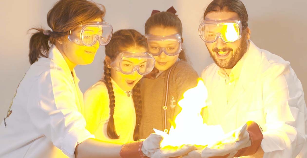 Kids and mad scientists wearing safety goggles looking at paper on fire